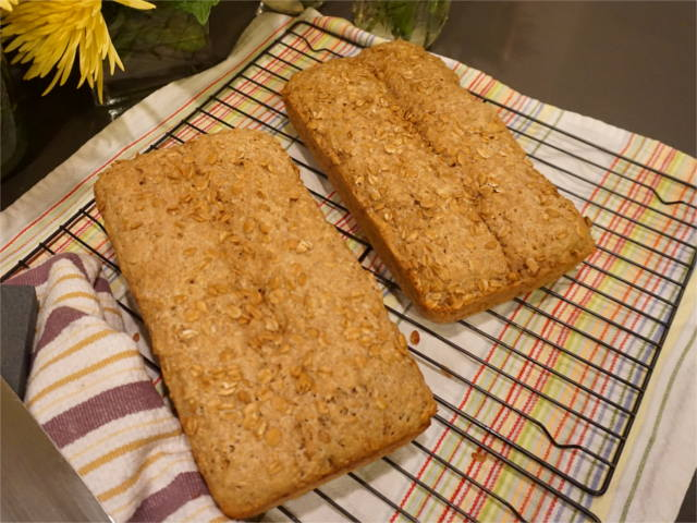 two loaves of spelt bread on a cooling rack