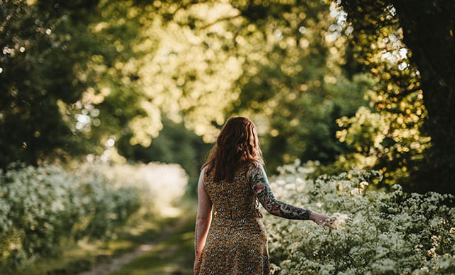 A woman walking in the countryside during the golden hour