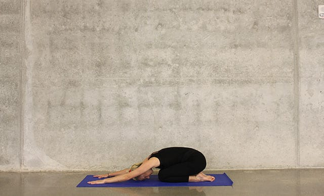 A woman in child's pose on a blue yoga mat