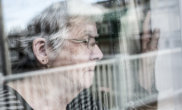 An elderly woman looking out a window