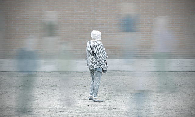 "An elderly woman with her back turned and blurry ""ghostlike"" images of people around her to suggest confusion and dementia"